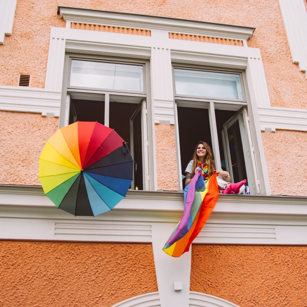 person in window with rainbow flag